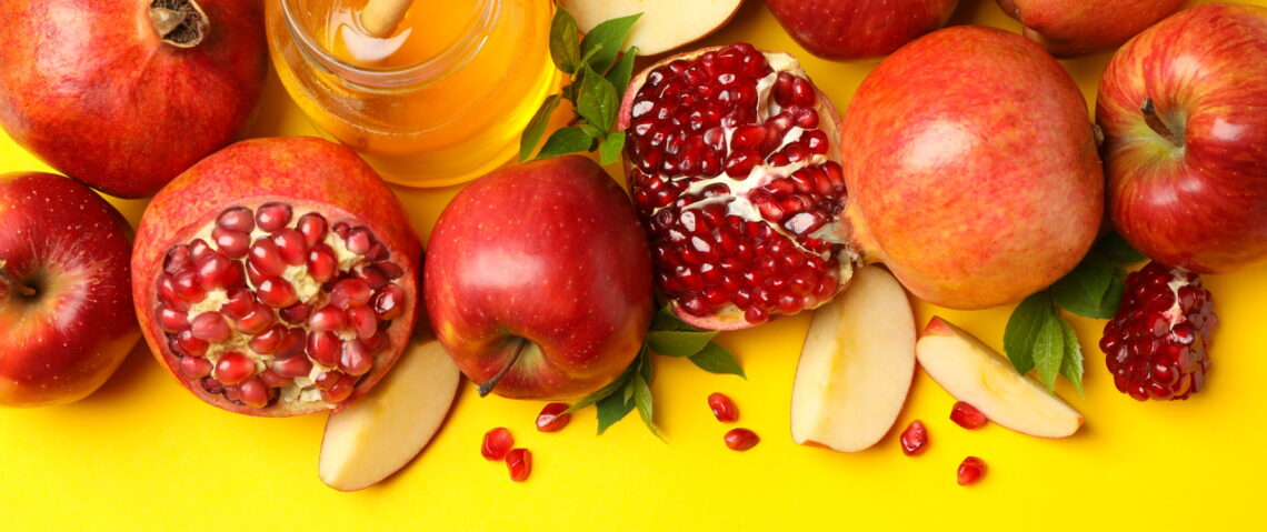 Apple, honey and pomegranate on yellow background, space for text